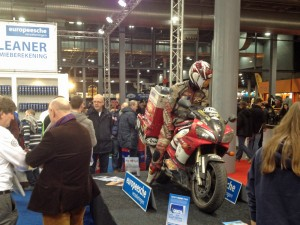 Stand van Europeesche Verzekeringen, MotorBeurs, Utrecht. Doorlopende R1-Wereldreis presentatie via hun apparatuur.
